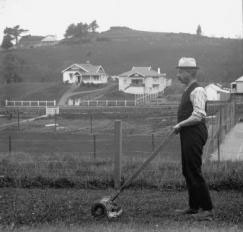 Figure 4: Unknown fellow pushing the handmower circa 1920, photo by Isaac Henry Bowen Jefarre. Alexander Turnbull Library. Ref. 1/2-077674-G.