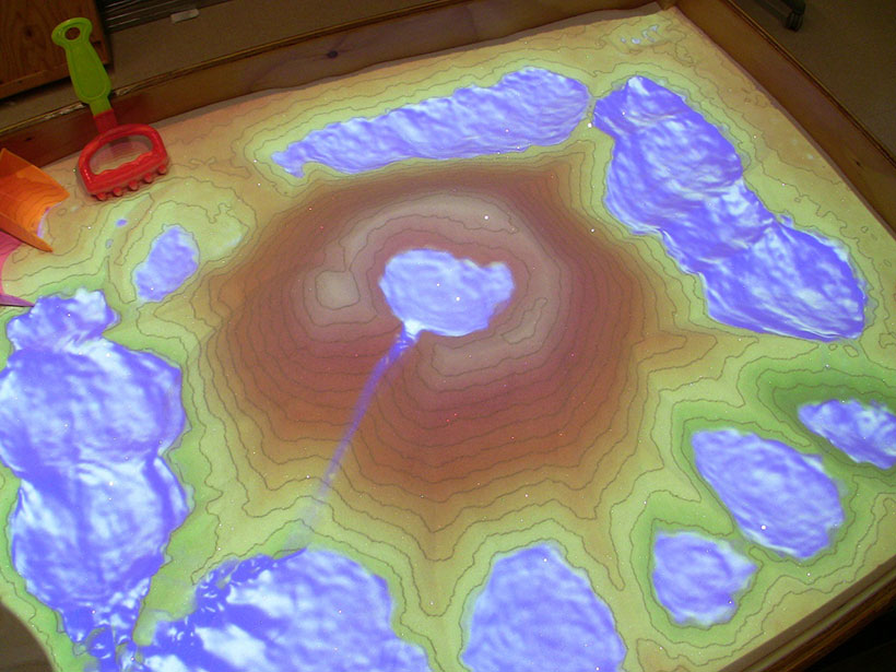 """Overhead view of the AR Sandbox showing augmented reality—contour lines and virtual water projected on sand """"landforms."""""""