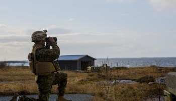 A member of the U.S. Marine Corps views the impact of a missile fired as part of NATO exercise Cold Response 16, a military-academia partnership.