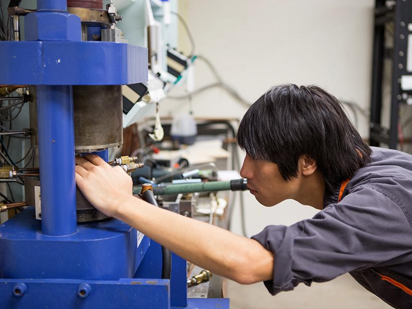 A visiting postdoc prepares for a high-pressure rock mechanics experiment in Texas A&M's rock deformation laboratory.