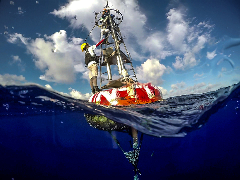 Technicians maintain an enhanced data buoy in the northwest Pacific, part of a new program to help monitor typhoons.
