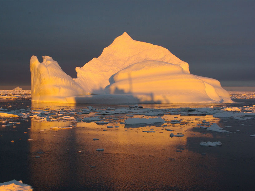 R/V Laurence M. Gould casts a shadow on an iceberg along the West Antarctic Peninsula.