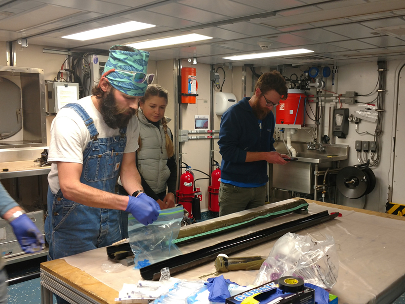 Participants in the UNOLS Chief Scientist Training Cruise split and examine sediment cores during the 2016 expedition.