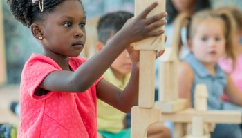 A young girl plays with blocks.