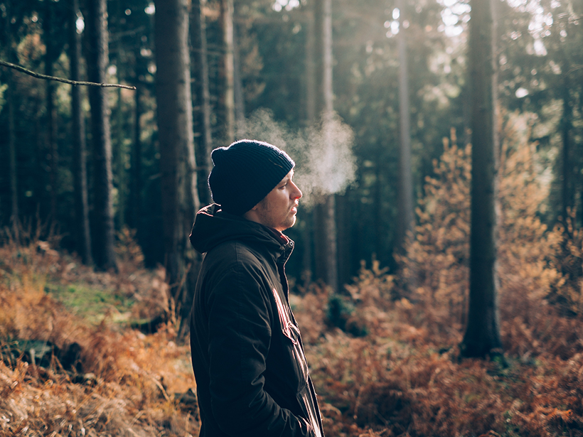 A man exhales in a forest