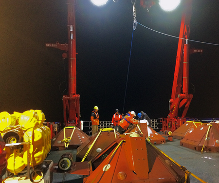 R/V Sikuliaq crew members deploy ocean bottom seismometers for measuring strain along the Aleutian subduction zone.