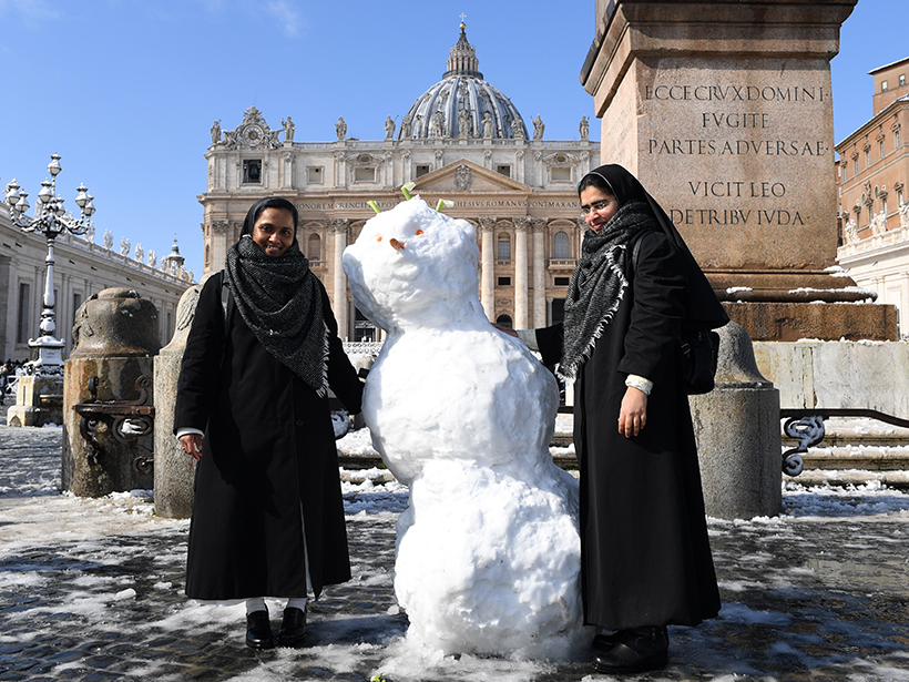 Nuns pose with a snowman at the Vatican in Rome on 26 February 2018.