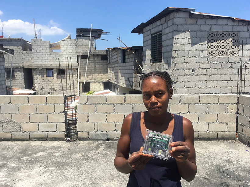 A woman displays a Raspberry Shake seismometer in front of construction typical of many neighborhoods in Haiti.