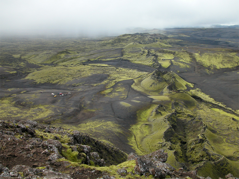 Aerial photo of a green volcanic landscape with cars