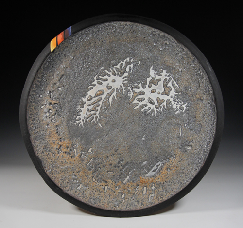 A ceramic platter coated with iron inspired by asteroid 16 Psyche