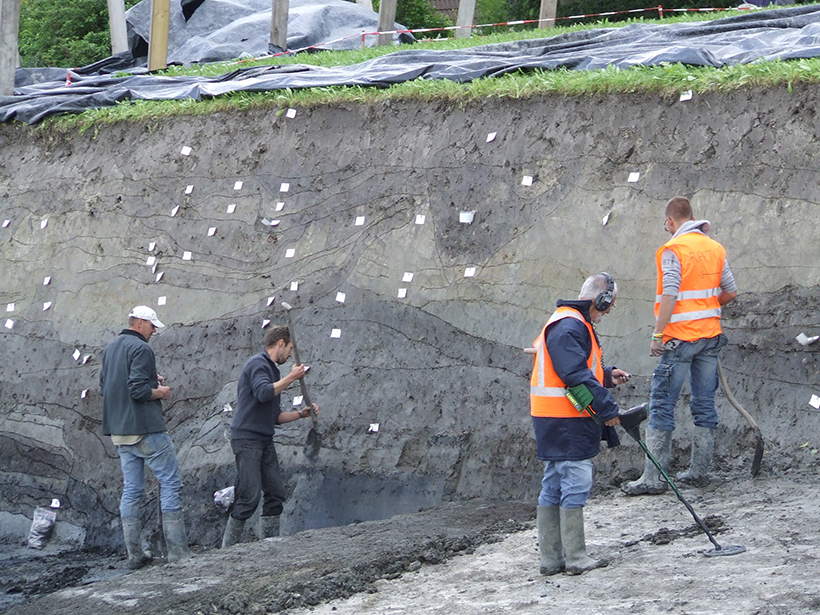 Workers excavate an earthy cliff beneath grassy turf.