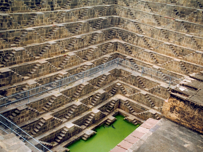 Photo of a deep stepwell in India, with a green pool at the bottom