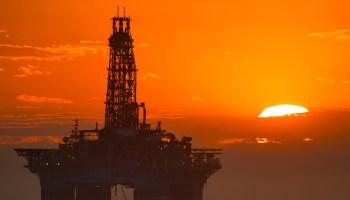 Orange sunset over ocean and offshore oil platform