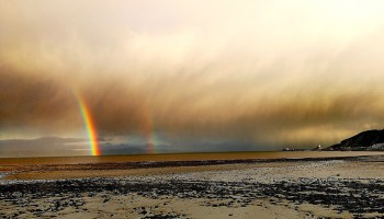 Clouds and rainbows hang over a broad beach on Britain's west coast.