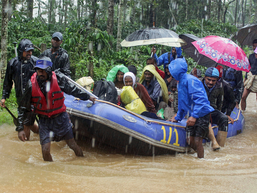 Flood victims are transported in an inflated raft as rain falls.