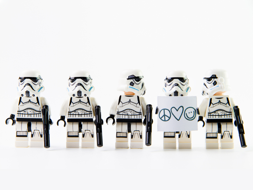 A lineup of five Lego stormtroopers, one carrying a peace/love sign