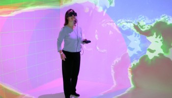Louise Kellogg wears a VR headset in a VR environment