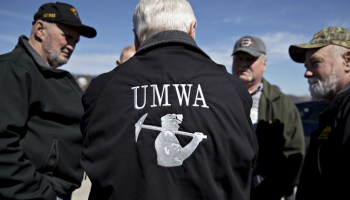 A man in a United Mine Workers of America jacket talks, back to the camera, with other men.