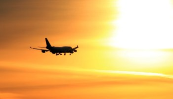 Plane flying into sunset