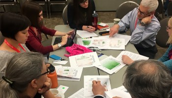 Practitioners participate in a group exercise around a table during a training session on using climate projections.