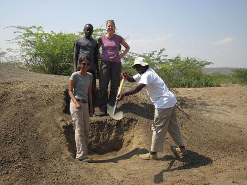 Four people near a rocky outcrop in Kenya