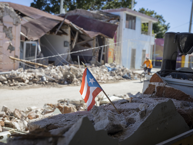 Damaged buildings with a Puerto Rican flag in the foreground