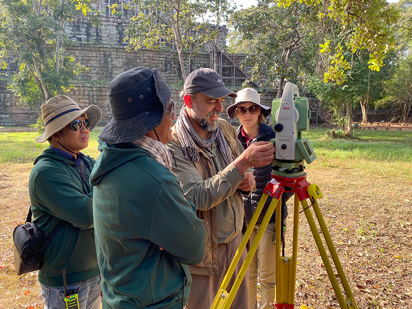 Anthropologists set up a total station to study a Khmer city complex.