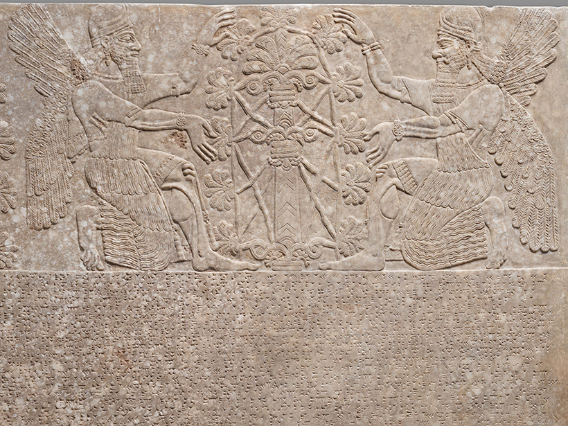 Carved Assyrian tablet with winged figures kneeling before a tree and cuneiform script beneath