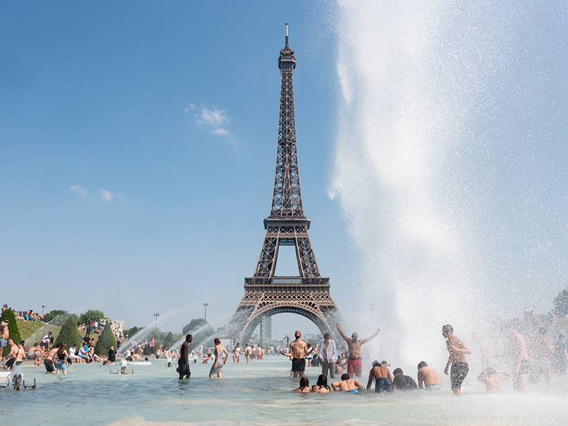 People play in a fountain overlooking the Eiffel Tower in Paris during a heat wave.
