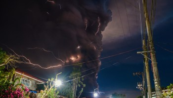 A volcanic ash plume with lightning towers over a residential neighborhood in the Philippines