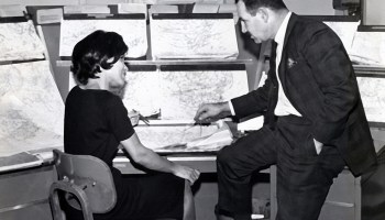 Black-and-white photo of a seated woman and man discussing large weather maps