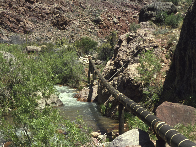 A pipeline stretches across a flowing river in a small canyon.