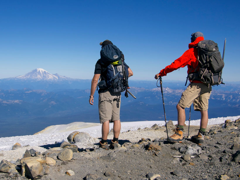 Two brothers equipped with backpacks and ice axes stand on the summit of Mount Adams (3,743 meters), admiring their next objective: Mount Rainier (4,392 meters), the tallest and most challenging of the Cascade volcanoes.