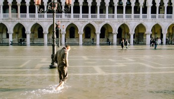 People wade through a foot of water in St. Mark's Square in Venice, Italy