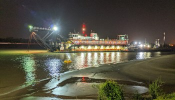 A dredge works through the night to clear shoaling along the Mississippi River at New Orleans.