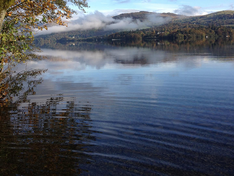 Placid view of Lake Windermere, Cumbria, and low rolling hills