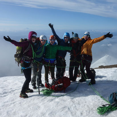 Group of women mountaineers cheer from the summit of Mount Baker, Washington.
