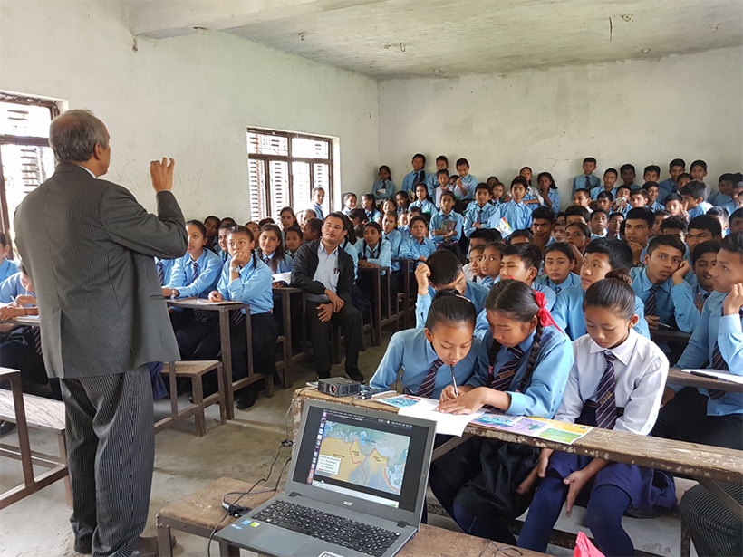 A man lectures to a room of attentive blue-shirted students in Nepal
