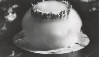 Black-and-white image of a nuclear bomb exploding from underwater