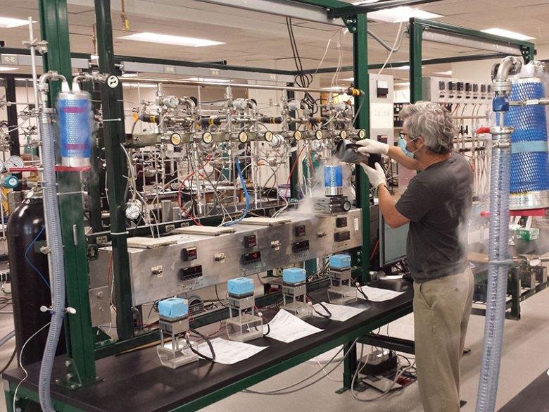 Man prepares air samples with a complex machine in a lab