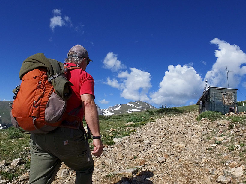 A man backpacks up a rocky trail to an air-sampling station