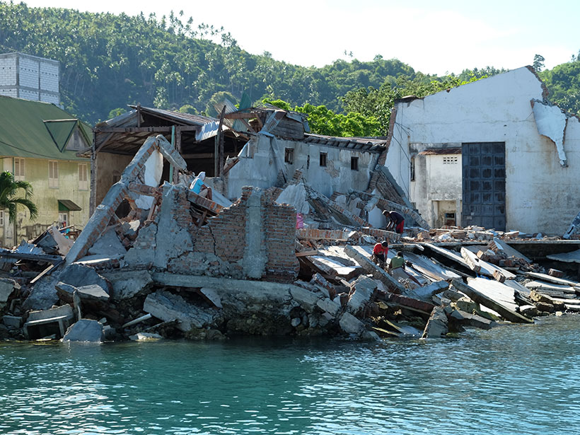 The toppled remains of a building on the shore of Palu Bay in Indonesia following a 2018 earthquake and tsunami