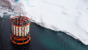 A rosette water sampler hangs from a cable above the Arctic Ocean surface near some sea ice
