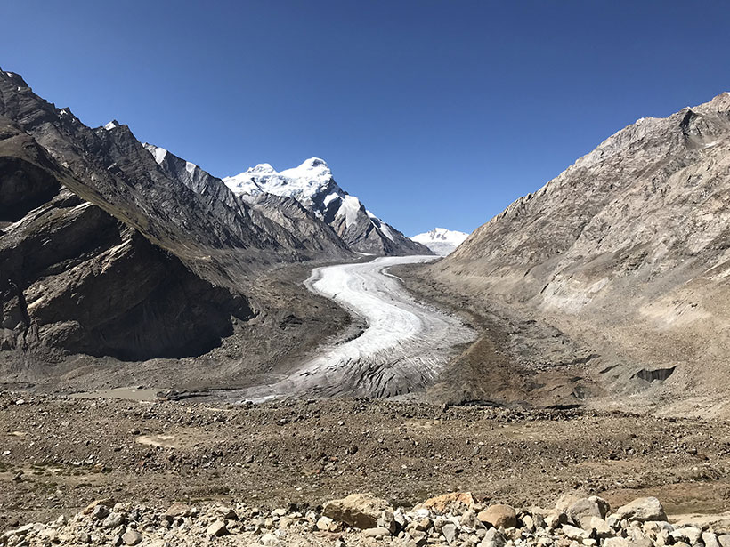 A glacier in the Zanskar region of northern India is flanked by dark lateral moraines as it flows between Himalayan peaks.