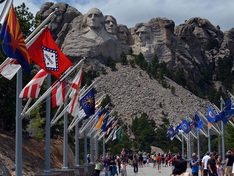 Four faces carved in granite stand above an apron of crushed rock overlooking state flags along the Avenue of Flags at Mount Rushmore National Memorial.