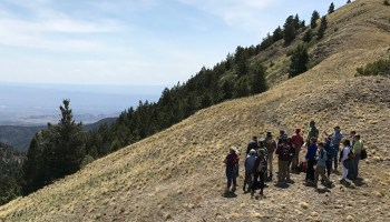 A group of people stand looking out to the horizon from a mountainside during an Incorporated Research Institutions for Seismology (IRIS) trip.