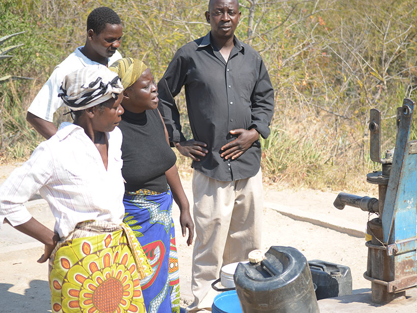 Two men and two women stand near a hand-pumped borehole in Manicaland, Zimbabwe.