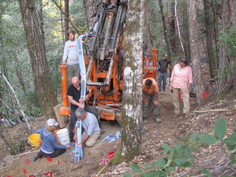 Researchers use heavy machinery to install a monitoring tube into the ground in a forest.