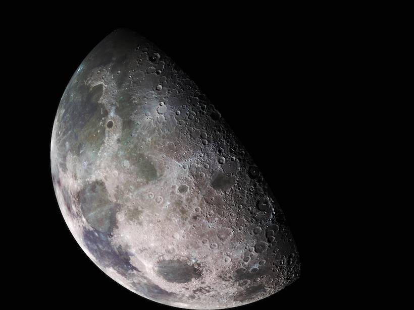 A color mosaic close-up of the pockmarked surface of a crescent Moon