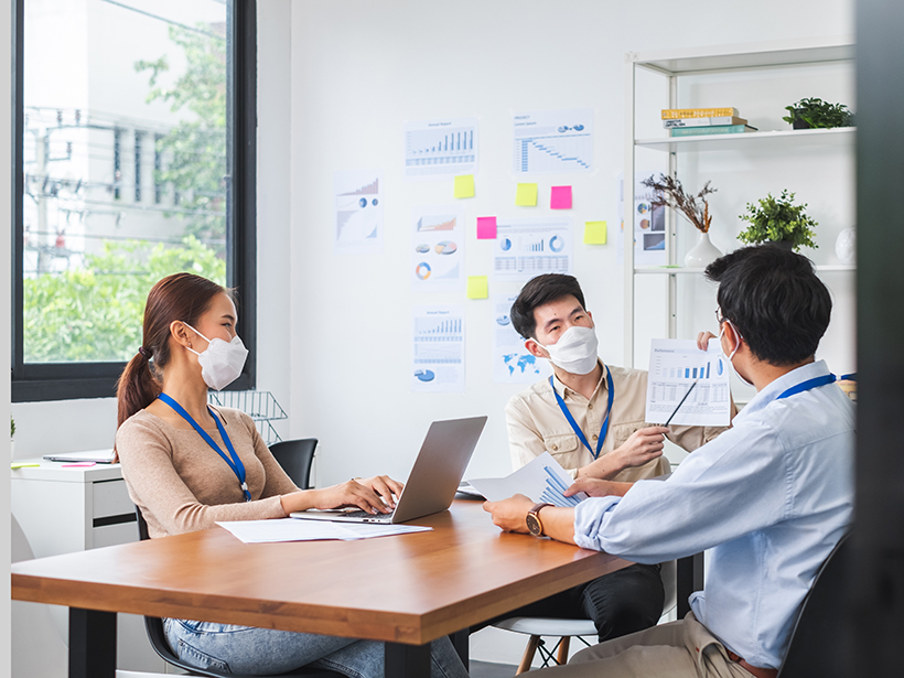 Colleagues meet in an office wearing masks.